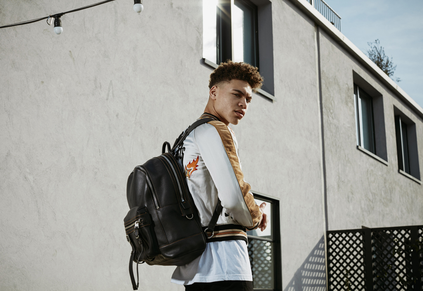 Brian Whittaker wears the Coach Snake and Star Souvenir Jacket and Coach Flag Backpack in black pebble leather.