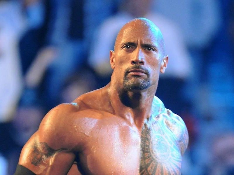 """Above: Dwayne """"The Rock"""" Johnson poses in the wrestling ring"""