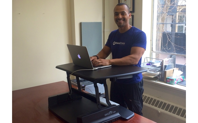 Above: Brent Bishop at his home office with his adjustable stand-up desk from Varidesk
