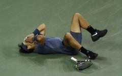 Rafael Nadal falls to the court after defeating Novak Djokovic (Photo: Julio Cortez/AP)