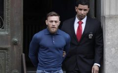 Ultimate fighting star Conor McGregor, left, is led by an official to an unmarked vehicle while leaving the 78th Precinct of the New York Police Department, Friday, April 6, 2018, in the Brooklyn borough of New York. McGregor is facing criminal charges in the wake of a backstage melee he allegedly instigated that has forced the removal of three fights from UFC's biggest card of the year. Video footage appears to show the promotion's most bankable star throwing a hand truck at a bus full of fighters after a Thursday news conference for UFC 223 at Brooklyn's Barclays Center. (AP Photo/Julio Cortez)